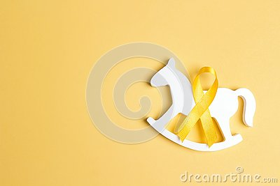 Children`s toy with a Childhood Cancer Awareness Yellow Ribbon on yellow background