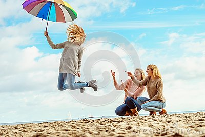 stock image of women jumping with umbrella