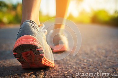 Feet of woman walking and exercise on the road