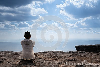 A person sitting on rocky mountain looking out at scenic natural view