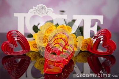 A bouquet of yellow roses and red plastic hearts. Valentine`s Day
