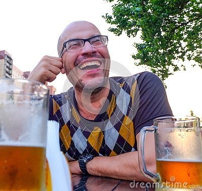 The man drinking cider jokes, smiles. A young man drinks cider in an open cafe and looks into the distance. Entertainment concept