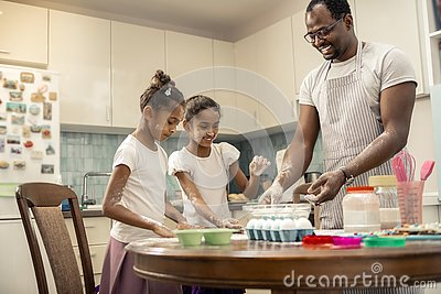 Two funny girls cooking pie with their loving helpful father