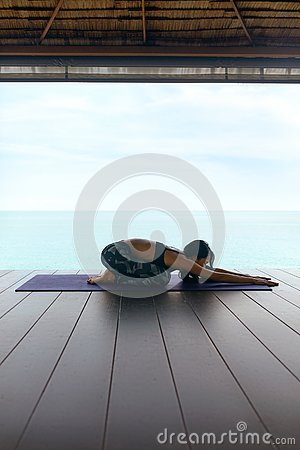 stock image of yoga training. woman in sport clothes stretching body near sea