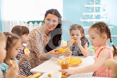 Kids and carer together eat fruit as a snack in the kindergarten, nursery or daycare