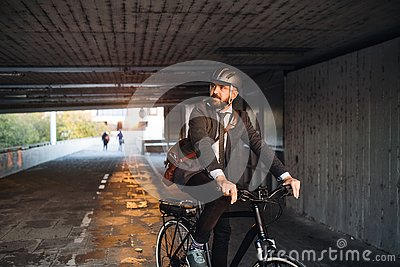 Hipster businessman commuter with electric bicycle traveling to work in city.