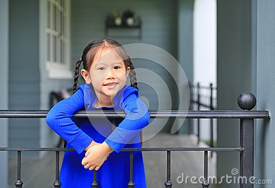 Happy little Asian child girl standing at house balcony bars and looking camera at the morning