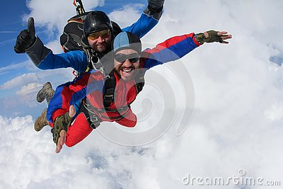 Skydiving. Tandem is flying in the clouds.