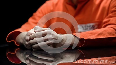 Hand of male prisoner, inmate giving evidence in detention room, cooperation