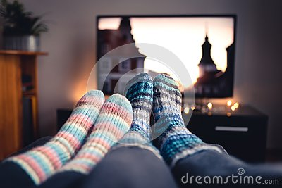 Couple with socks and woolen stockings watching movies or series on tv in winter. Woman and man sitting or lying together on sofa.