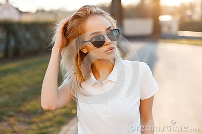Modern stylish young hipster woman in trendy white polo t-shirt in black sunglasses stand and posing