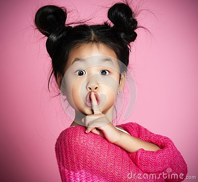 Asian kid girl in pink sweater shows shh sign Close up portrait