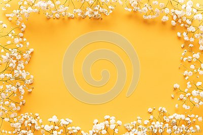 Bright yellow paper background with soft little white flowers, welcome spring concept. Happy Mothers Day, Womens Day greeting card