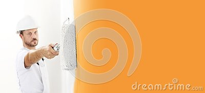 Painter man at work with a paint roller, wall painting concept, view from top on copy space template