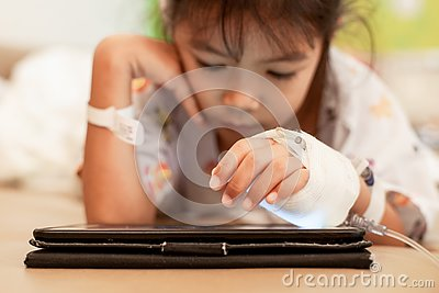 Sick asian little child girl who have IV solution bandaged playing digital tablet to relax