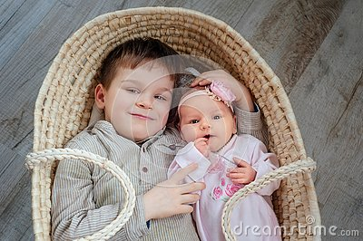 Children, cute little boy 5 years old, with him newborn sister lies in a wicker cradle