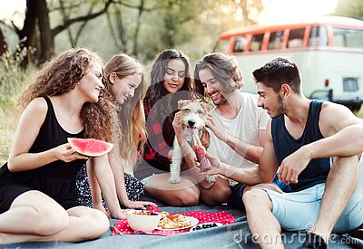 A group of friends with a dog sitting on ground on a roadtrip through countryside.