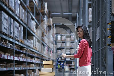 stock image of in warehouse storage, asia woman carrying shop cart for shopping and select to buy home interior appliances
