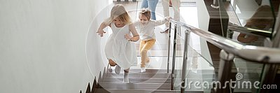 Children going upstairs to second floor their new modern house