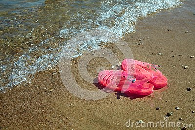stock image of pink women`s jelly sandals on a sea shore. ladies flat jellies summer beach shoes.