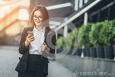 Portrait of cheerful young woman talking on smartphone and laughing outdoors. Happy beautiful caucasian woman using