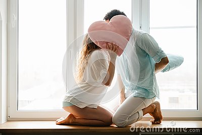 Couple girl and guy play with pillows near window.