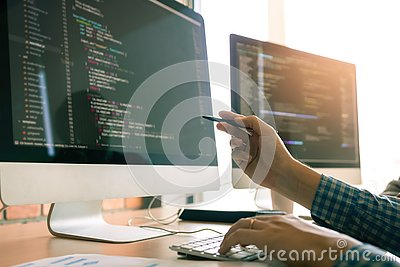 Developing programming working in a software engineers code tech applications on desk in office room