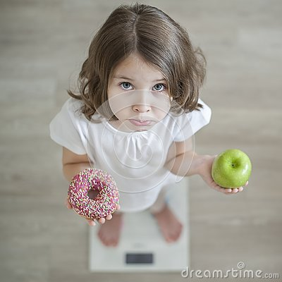 Right choice. Little sad girl holding in hands green apple and highcalorie donut. Kid trying to make decision between healthy
