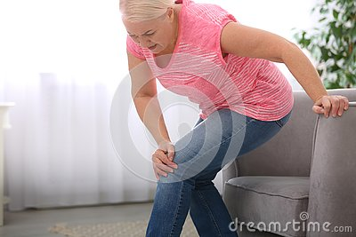 Senior woman suffering from knee pain in living room.