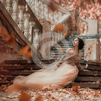 Great-looking charming dark-haired brunette girl sitting alone on the stone steps of an amazing royal castle, pretty