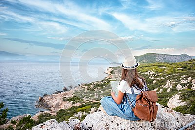 Hipster young girl with bright backpack enjoying panoramic mountain sea, using map and looking distance. Tourist traveler on