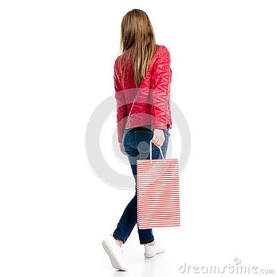 Beautiful woman in jacket and jeans in hand bag package goes