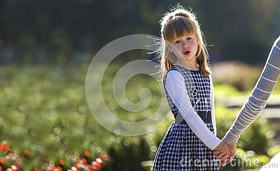 Moody cute child girl holding mother hand looking back on warm day outdoors. Family relationship and recreation