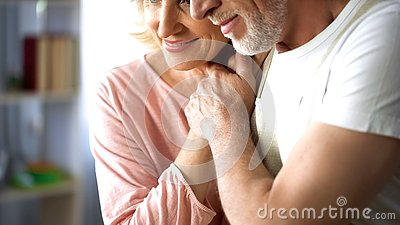 Happy married couple holding hands, old age togetherness, love and understanding