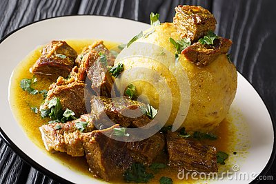 Puerto Rican Mofongo made from plantains, garlic and chicharron served with meat and broth close-up. horizontal