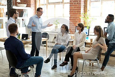 Diverse employees listening to male manager speaking at group meeting