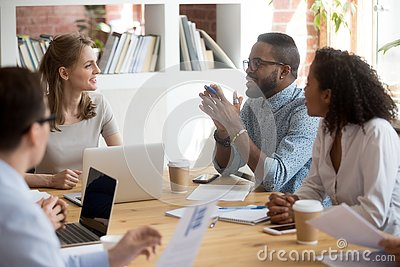 African male employee speaking sharing ideas at diverse team meeting