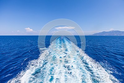 Wake of water from a boat, open sea with horizon and blue sky