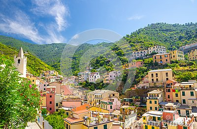 Colorful multicolored buildings houses on green hill in valley of Riomaggiore traditional typical Italian fishing village in Natio
