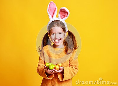 Funny happy child girl with easter eggs and bunny ears on yellow