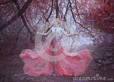 Attractive girl with gorgeous blond hairdo in the forest near the branches of trees, dressed in a light amazing pink