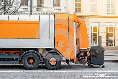 Garbage disposal lorry at city street. Waste dump truck on town road. Municipal and urban services. Waste management, disposal and