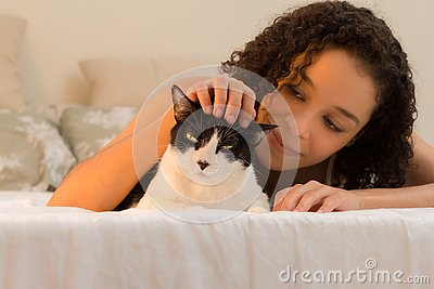 Girl with curly hair smiling at domestic cat pet in bed. Concept of love to animals, pets, lifestyle, care, tranquility, peace,