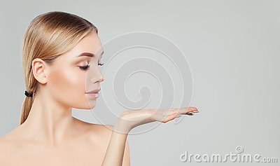 Pretty blonde woman showing her empty open hand with copy space for advertising marketing or product placement. Beauty girl