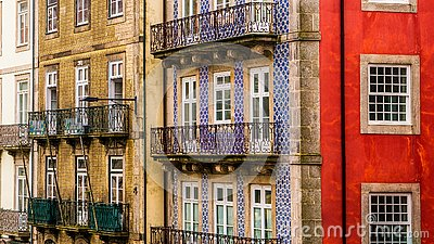 Row of old, colorful buildings with ornate balconies and tiles line a street in Porto, Portugal