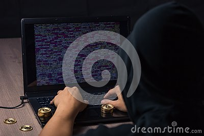 Hooded hacker using laptop to steal bitcoin