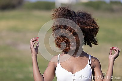 Front view of a beauty mixed race african american woman with hair blowed in air smiling at camera dancing in movement