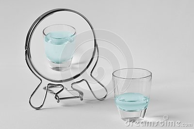 Half-empty water glass looking in the mirror and seeing himself as a full glass - Concept of optimism