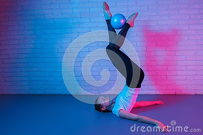 stock image of charming young slim gymnast woman in sports clothing exercises in front of brick wall in neon lights. flexible fit woman