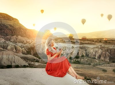 A girl sitting on the top of a cliff with a glass of Turkish tea at dawn with a view of the mountains of Cappadocia and balloons i